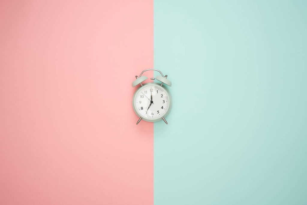 white alarm clock against a pink and blue background